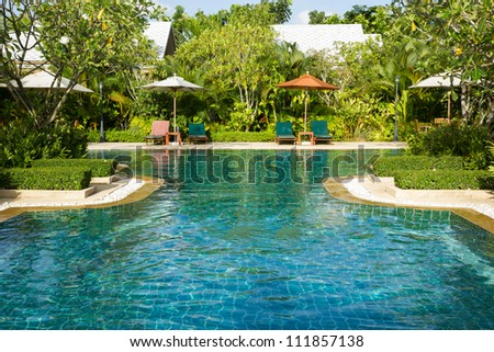 Swimming pool with relaxing seats and sun umbrella - stock photo