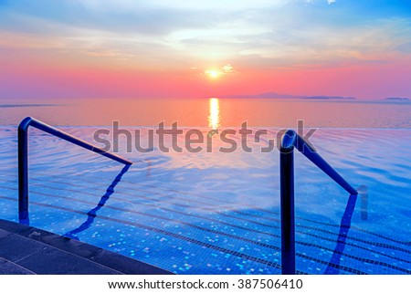 Swimming pool with stair and Panoramic dramatic tropical sunset on the sea at twilight times - Vintage Filter - stock photo