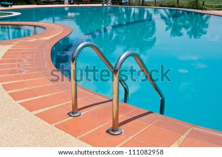 Swimming pool with stair at  resort - stock photo