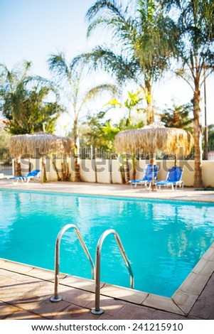 Swimming pool with stair, umbrellas, chairs and palm trees at the background. Shallow depth of field. - stock photo