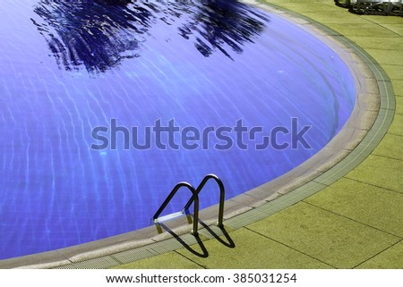 Swimming pool with stairs at hotel close up - stock photo