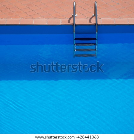 Swimming pool with steps. Looks enticing on a hot day. Simple composition with horizontal stripes, lines. - stock photo