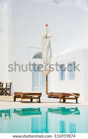Swimming pool with sunbeds at Oia,Santorini island,Greece - stock photo