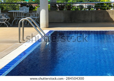 Swimming pool with sunny reflections on good weather day. Relax time with family on swimming pool. Popular sport.