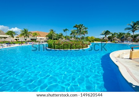Swimming pool with the tropical style island and dark blue sky and water at the luxury mexican resort. Bahia Principe, Riviera Maya.