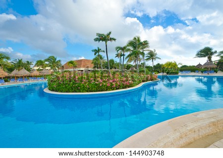 Swimming pool with the tropical style island at the luxury mexican resort. Bahia Principe, Riviera Maya.