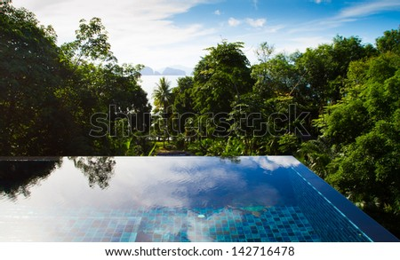 swimming pool with tropical forest view - stock photo
