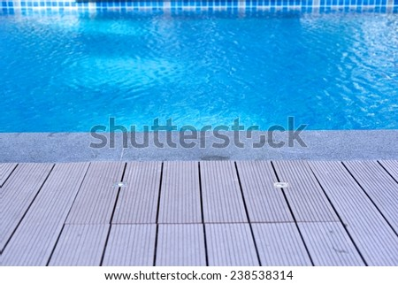 Swimming pool with wooden deck - stock photo