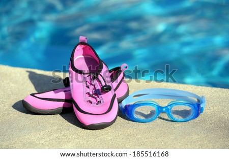 Swimming shoes and goggles in a swimming pool - stock photo