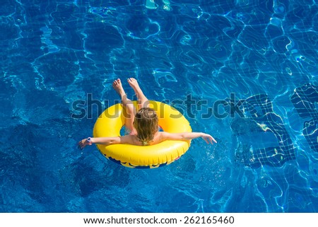 Swimming, summer vacation - lovely girl playing in blue water (space for text) - stock photo