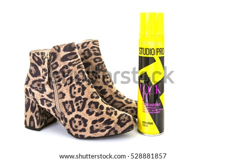SWINDON, UK - DECEMBER 4, 2016: Pair of Leopard Skin Boots with a can of Loreal Studio Pro Lock It hair spray