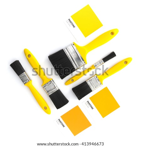 SWINDON, UK - MAY 2, 2016: Collection of yellow paint brushes with Pantone colour samples on a white background flatlay