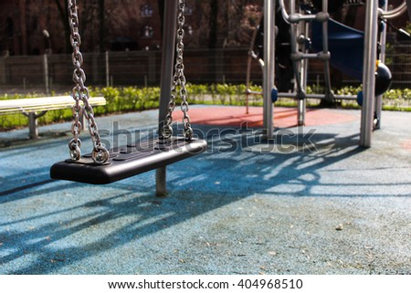 Swing at the playground at sunny day. The close picture of children's swings. - stock photo