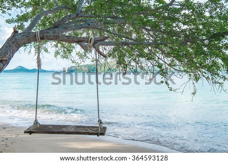 Swing hanging on tree on the beach - stock photo