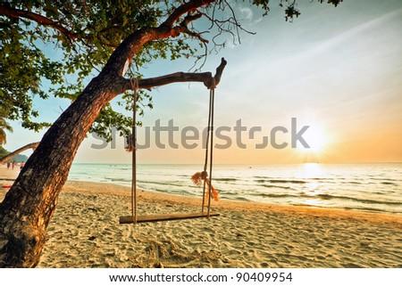 Swing on beautiful sunset at the beach - stock photo