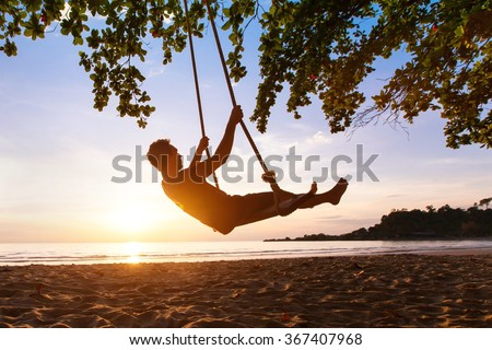swing on paradise tropical beach at sunset, happy people enjoying summer - stock photo