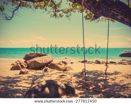Swing on summer beach with blue sky and turquoise sea, vintage filter effect - stock photo