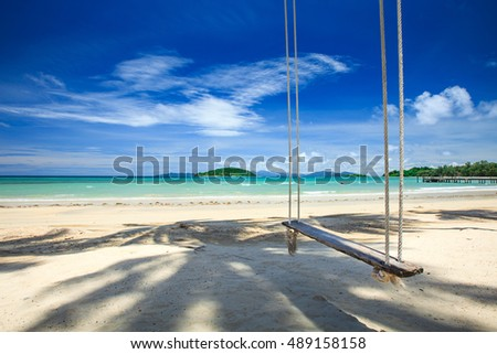 Swing on the beach over blue sky