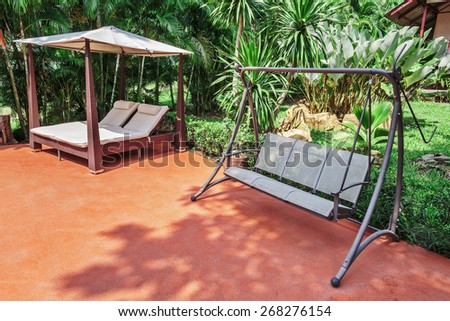 Swing on the patio in a tropical garden - stock photo