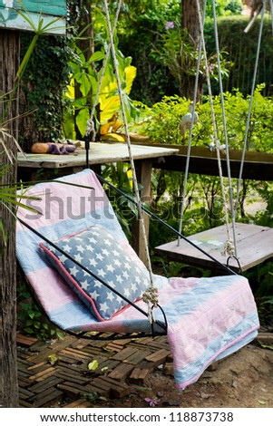Swing seat with pillow in the garden - stock photo