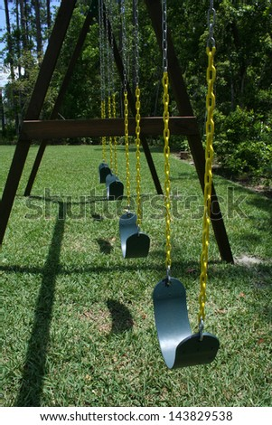 Swing set in Spring with nobody swinging - stock photo