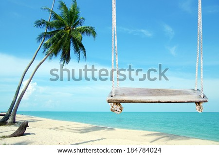 Swings on the sand tropical beach. - stock photo