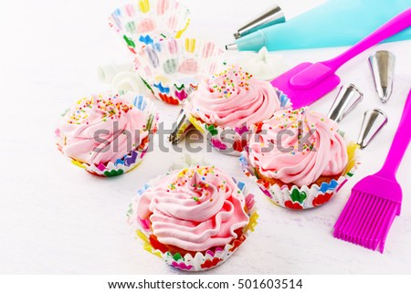 Swirl cupcake with whipped cream frosting and confectionery syringe. Birthday cupcake with pink whipped cream. Homemade decorated cupcakes.