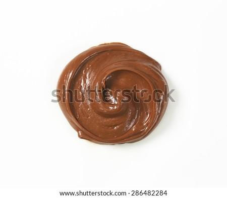 swirl of chocolate spread on white background - stock photo