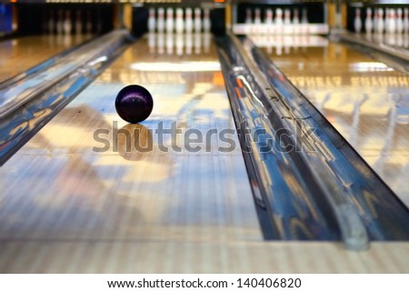 Swirling bowling ball is rolling down the path to the bowling pins - stock photo