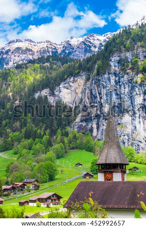 Swiss Alps and green fields in famous touristic town with high waterfall in background. Lauterbrunnen, Switzerland,Europe.
