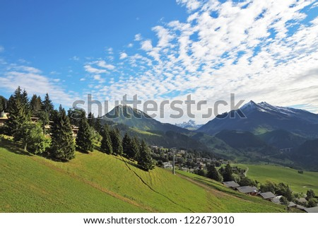 Swiss Alps. Green alpine meadow on a hillside and surrounded by pine forests - stock photo