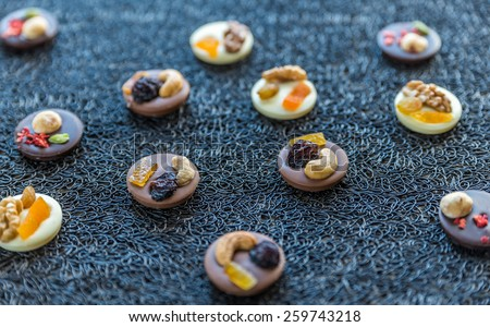Swiss chocolate candies with nuts and dried fruits - stock photo