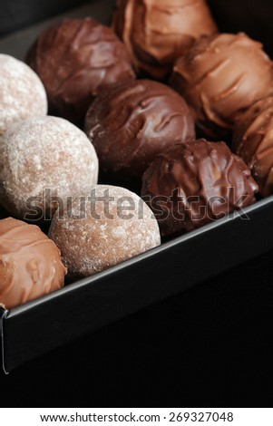 Swiss chocolates assorted in a gift box, on black background with empty space for text - stock photo