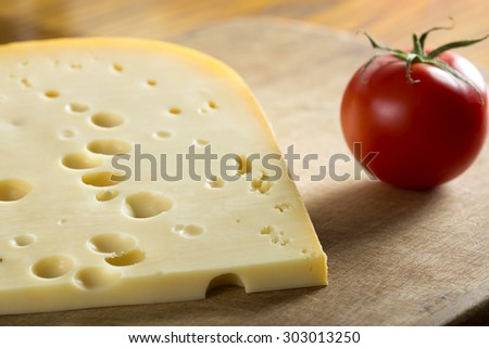 Swiss Emmental Cheese and tomato over wood background - stock photo