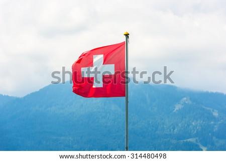 Swiss flag against Alps mountains. Horizontal shot - stock photo