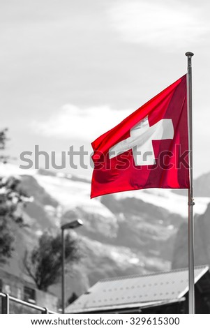 Swiss flag against Alps mountains. Partly colored shot - stock photo
