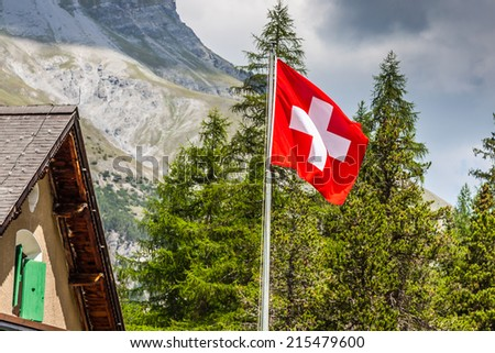 Swiss flag - national symbol of Switzerland with Alps in background - stock photo