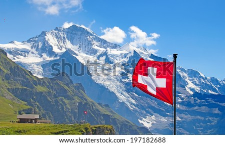 Swiss flag on the top of Mannlichen (Jungfrau region, Bern, Switzerland) - stock photo