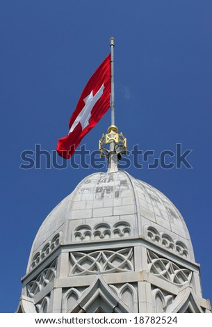 Swiss flag on top of the Grossmunster tower, Zurich, Switzerland - stock photo