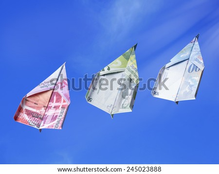 Swiss Franc banknotes as toy planes rising high in the sky  - stock photo