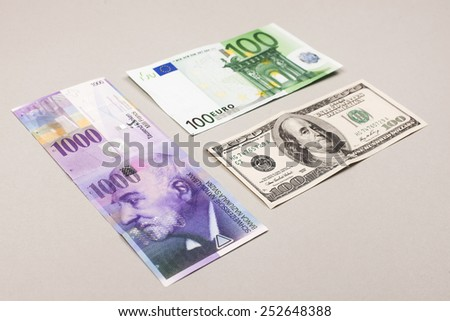 swiss francs, euro and dollars. money from switzerland in europe on grey background - stock photo