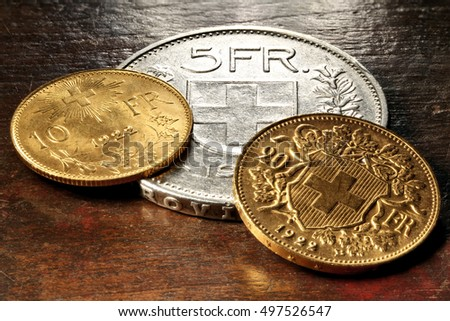 Swiss gold and silver coins on rustic wooden background