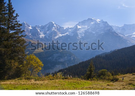 Swiss meadow and mountain with hikers in distance moving through valley - stock photo