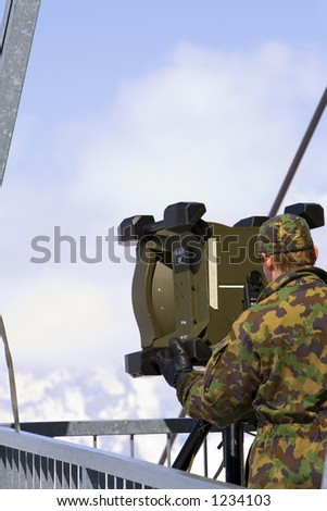 Swiss military man is setting a communication device
