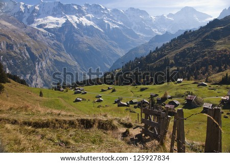 Swiss trail and fence with valley and Alpine mountains - stock photo