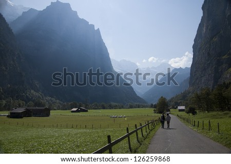 Swiss valley and farmland with two hikers walking down path towards distant mountains
