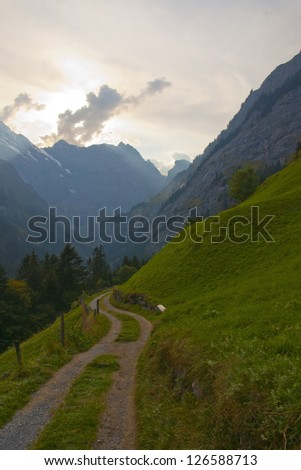 Swiss valley and mountains with cloud blocking bright sunlight
