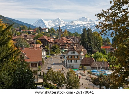 Swiss village with snowy peaks on the background - stock photo