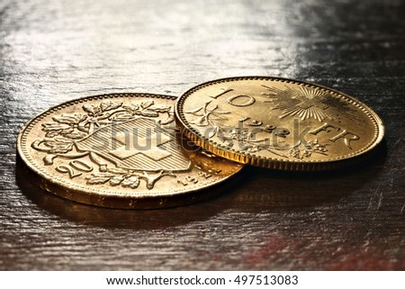Swiss Vreneli gold coins on rustic wooden background