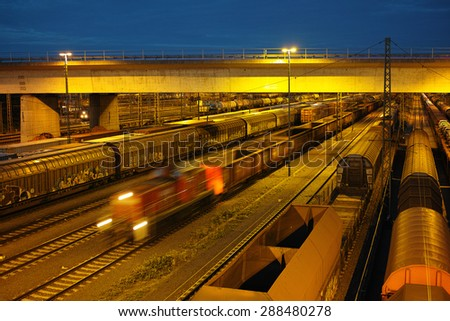switch yard with trains, wagons, cargo at night - stock photo